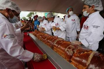 Cooks add the finishing touches to the world's largest Pan de Jamón in Caracas, Venezuela, Saturday, Nov. 15. Hundreds of cooks and spectators were on hand for the creation of the Pan de Jamón, a Christmas specialty in which ham is rolled in sweet bread, as well as the world's biggest hallaca, a local take on the tamale traditionally eaten in December. (AP photo)