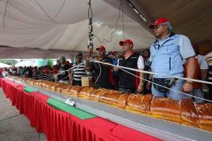 Officials weigh the world's largest Pan de Jamón in Caracas, Venezuela, Saturday, Nov. 15. Hundreds of cooks and spectators were on hand for the creation of the Pan de Jamón, a Christmas specialty in which ham is rolled in sweet bread, as well as the world's biggest hallaca, a local take on the tamale traditionally eaten in December. (AP photo)