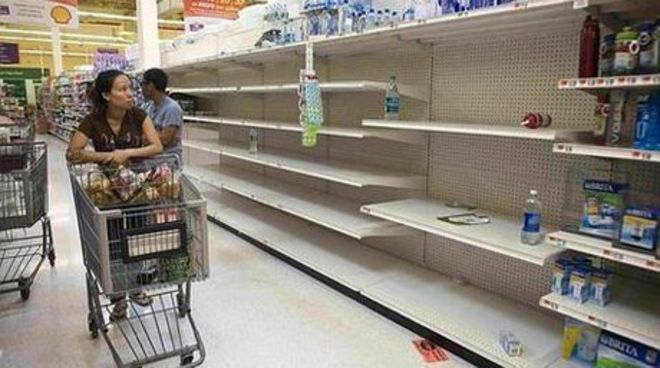 "The original high resolution photo. Original caption: ""A shopper passes empty shelves while looking for bottled water at a Stop and Shop at Rockaway Beach in New York, August 26, 2011. As North Carolina braced on Friday for a direct hit from Hurricane Irene, cities along the East Coast were on alert and millions of beach goers cut short vacations to escape the powerful storm. With more than 50 million people potentially in Irene's path, residents stocked up on food and water and worked to secure homes, vehicles and boats. States, cities, ports, oil refineries and nuclear plants scrambled to activate emergency plans."" (Allison Joyce/Reuters)"